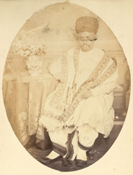 Full-length seated portrait of a man of the Bhatia caste, Bombay.